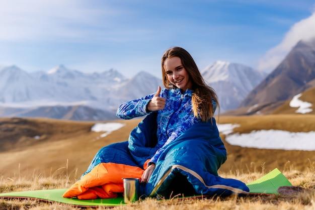 행복한 여성 관광객은 산을 배경으로 앉아 있다
