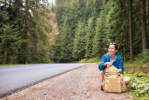 幸せな女性の観光客はバックパックを背負って道端に座っています。旅行や夏休みのアウトドアライフスタイルのコンセプト
