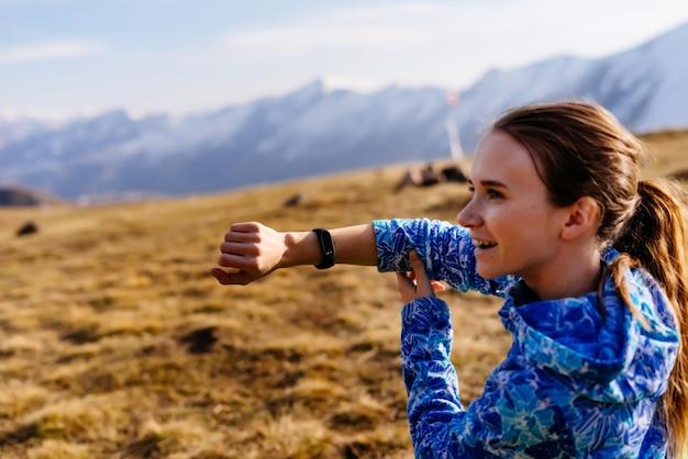 Happy woman tourist sits showing fitness bracelet