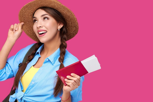 Happy woman tourist in summer casual clothes holding passport and airplane vacation tickets on holiday on pink isolated background