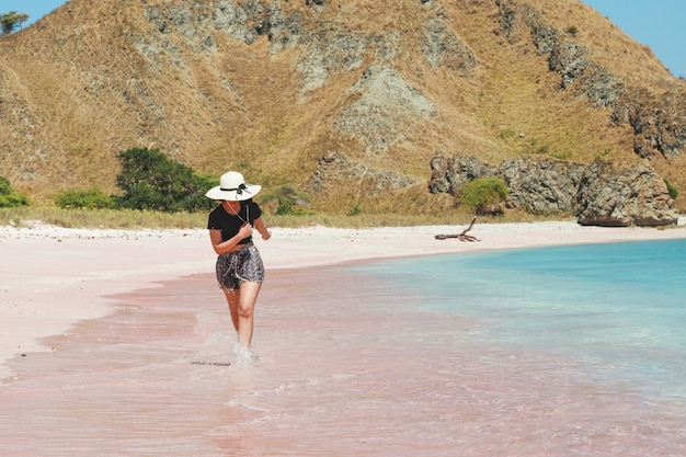 Happy woman tourist in summer hat running on pink sandy beach at labuan bajo