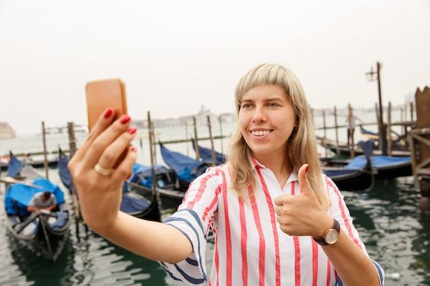 Счастливая женщина турист принимая selfie портрет с гондолами в венеции, италия