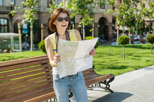 Happy woman tourist travel holding camera and map