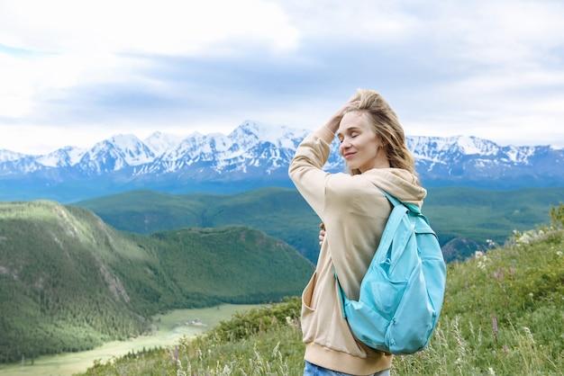 산에서 배낭을 메고 행복한 여성 관광