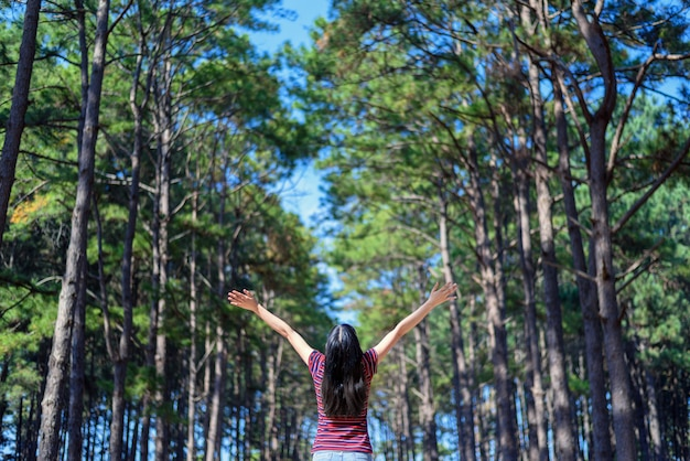 Happy woman touristraised hand in pine forest