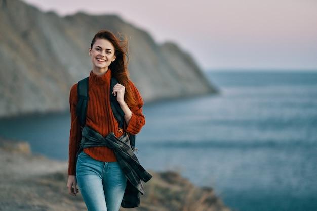 幸せな女性の観光客は山のトリミングされたビューで海の近くを旅行します