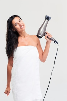 Happy woman in towel holding hairdryer