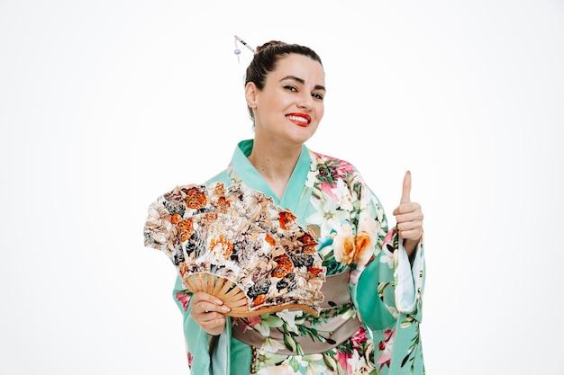 Donna felice in kimono giapponese tradizionale che tiene ventaglio sorridente che mostra ampiamente il segno ok su bianco