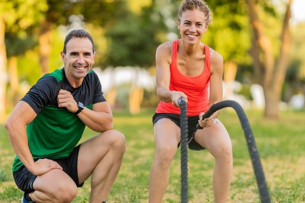 그녀의 개인 트레이너와 함께 공원에서 훈련하고 전투 밧줄을 사용하는 행복한 여자.