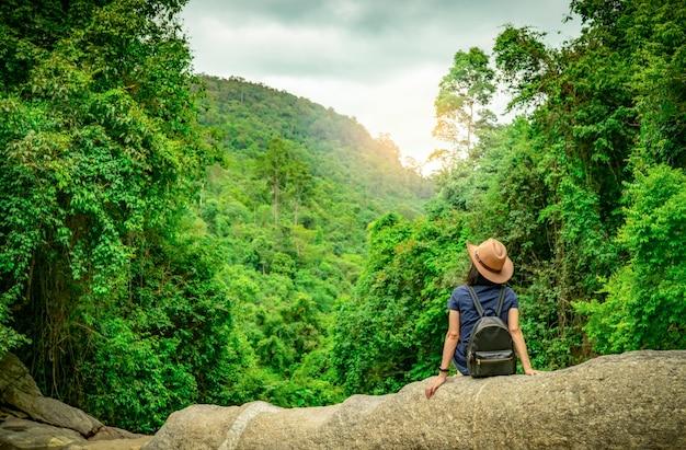 幸せな女は森の中で一人で旅行します。気分が良いアクティブな女性は、森の中の密な木と緑の谷の石の上に座っています。幸せな休暇。幸せな女の背面図は、バックパック、スマートバンドを着用します。