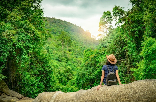 Happy woman travel alone in woods. active woman with good mood sit on stone in green valley with dense tree in the forest. happy vacation. back view of happy woman wear backpack, smart band.