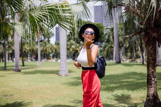 緑の芝生の上の熱帯公園で美しい晴れた日を楽しんで、バックパックを持ってバンコクを旅する幸せな女性