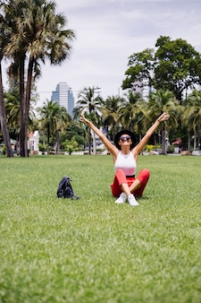 녹색 잔디 필드에 열대 공원에서 아름다운 화창한 날을 즐기는 배낭과 함께 방콕 주변의 행복한 여자 여행