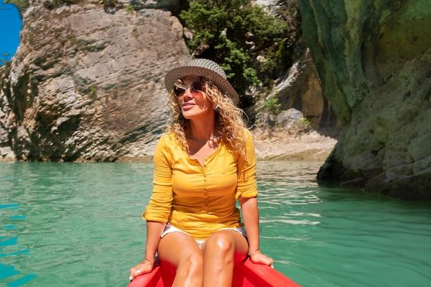 緑の水の川と美しい峡谷の赤いカヌーに座って楽しんでいる幸せな女性旅行者のライフスタイル-楽しい無料の女性の人々は休暇で楽しんで旅行を楽しんでいます