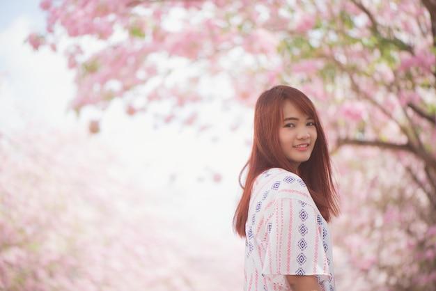 행복한 여자 여행자는 휴가에 벚꽃이나 사쿠라 꽃 나무와 함께 무료로 휴식을 취
