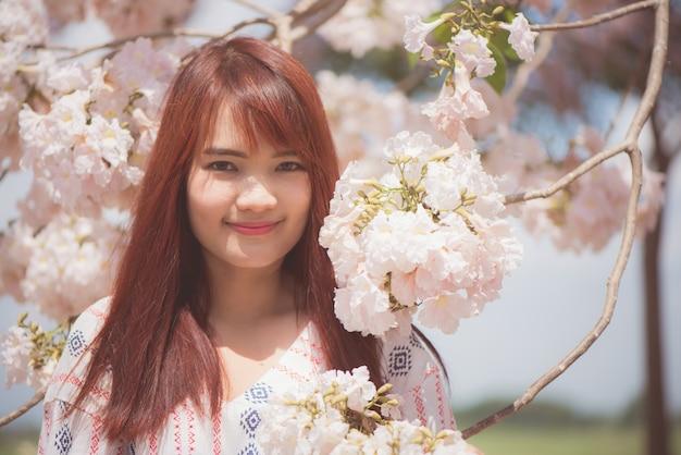 幸せな女性の旅行者は休暇で桜やサクラの花の木を自由に感じる