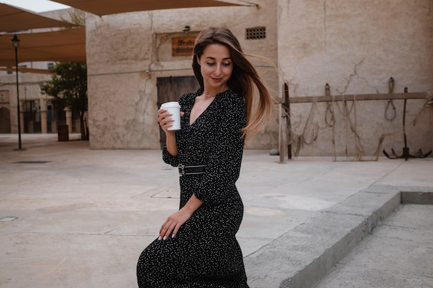 Happy woman traveler wearing black dress walking through the streets of an old arab town or village in the middle of the desert. coffee in a white cup, enjoying traditional arabic coffee