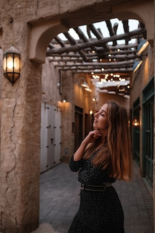 Happy woman traveler wearing black dress walking through the streets of an old arab town or village in the middle of the desert. traditional arabic oil lamps in al seef dubai street