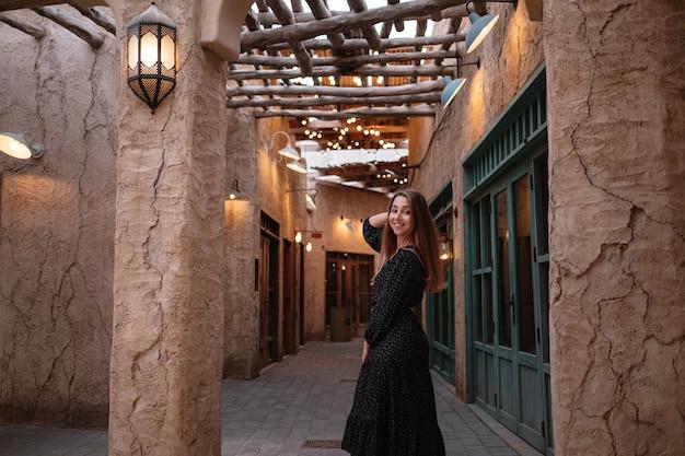砂漠の真ん中にある古いアラブの町や村の通りを歩いて黒いドレスを着て幸せな女性旅行者。アルシーフドバイ通りの伝統的なアラビアの石油ランプ