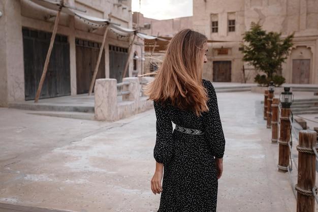 砂漠の真ん中にある古いアラブの町や村の通りを歩いて黒いドレスを着て幸せな女性旅行者。