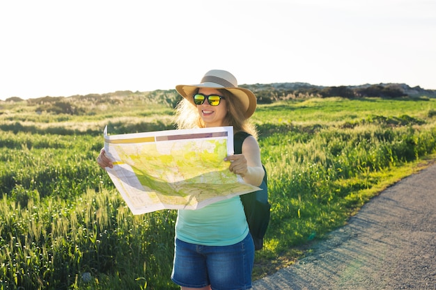 Happy woman traveler with backpack checks map to find directions
