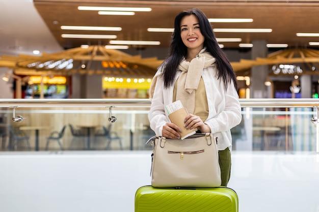 Счастливая женщина-путешественница с документами и билетом в ожидании вылета в терминале международного аэропорта