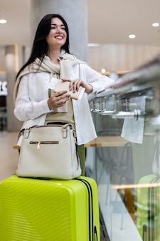 Happy woman traveling with green suitcase waiting departure boarding at airport terminal