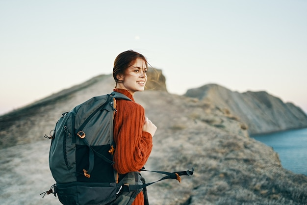 幸せな女性は海の風景の近くの自然の中で山を旅します