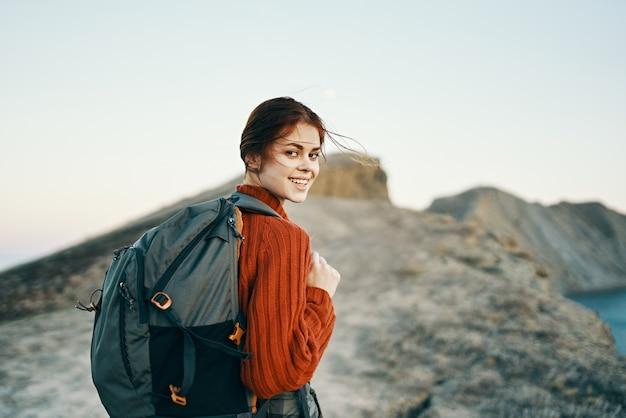 幸せな女性は海の風景の近くの自然の山を旅します高い石を揺るがします