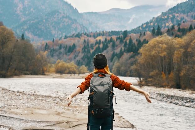 幸せな女性は秋の自然の中で山の川の近くを旅し、彼女の手でジェスチャー