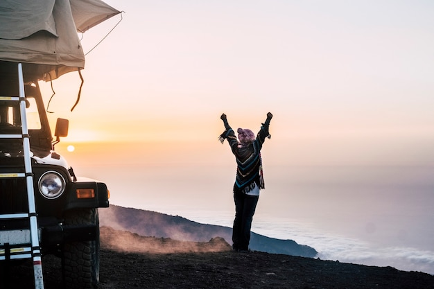 행복한 여자는 산 꼭대기에서 일몰을 즐기는 야생 장소에서 자동차와 텐트 지붕으로 여행합니다.