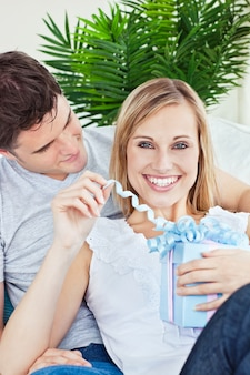 Happy woman unwrapping a present lying on the sofa with her boyfriend