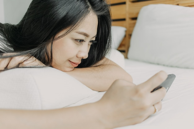 Happy woman use smartphone and relax on her bed.