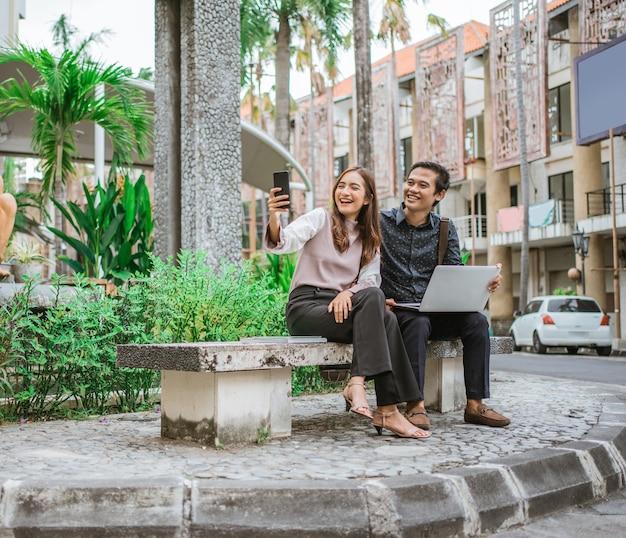 彼女のパートナーと自分撮りとビデオ通話を取っているスマートフォンを使用して幸せな女性