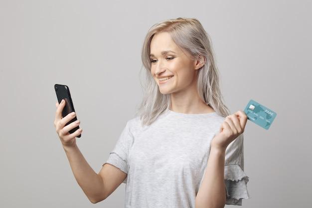 Счастливая женщина с помощью кредитной карты и смартфона для покупок в интернете.