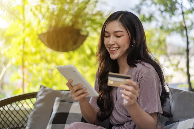 Happy woman using credit card to shopping online with tablet at cafe