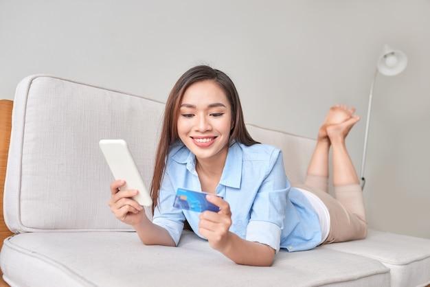 거실에서 신용 카드로 온라인 쇼핑을 위해 디지털 태블릿을 사용하는 행복한 여성