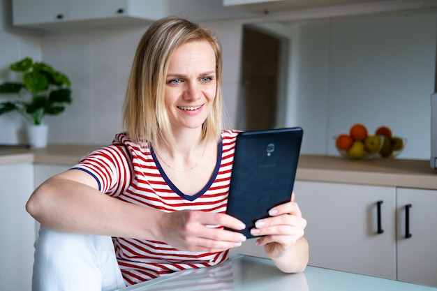 Happy woman using digital tablet for video call friends and parents, smiling girl sitting at home kitchen fun greeting online by computer webcam making videocall
