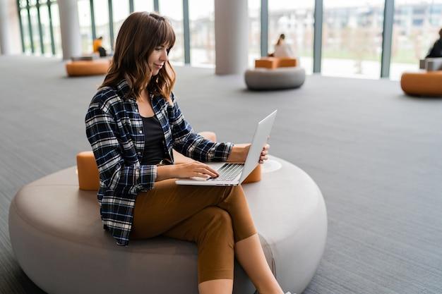 Счастливая женщина, используя портативный компьютер, сидя в зале ожидания аэропорта.