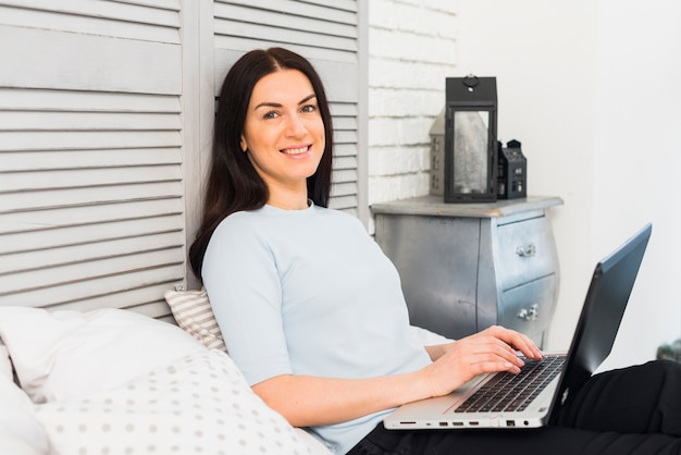 Happy woman using laptop on bed