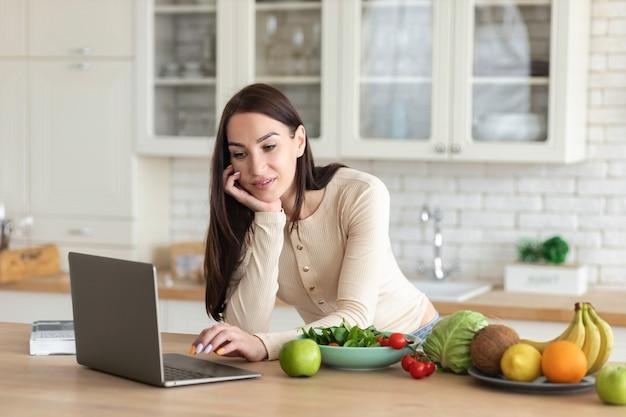 食事の準備のための食品のセットと家庭の台所でラップトップを使用して幸せな女性