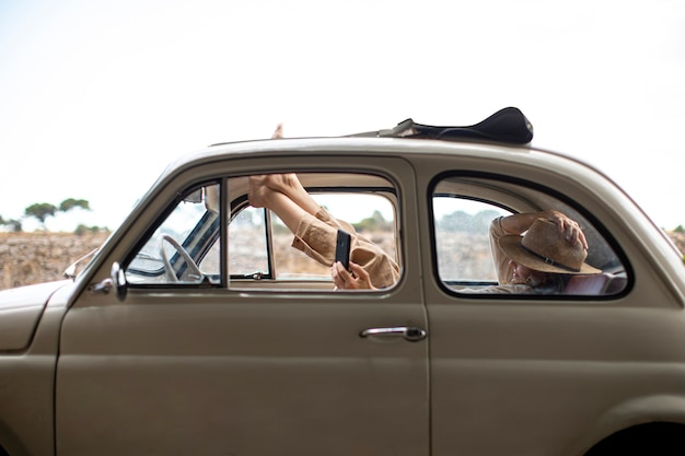 Happy woman using at mobile phone inside retro car
