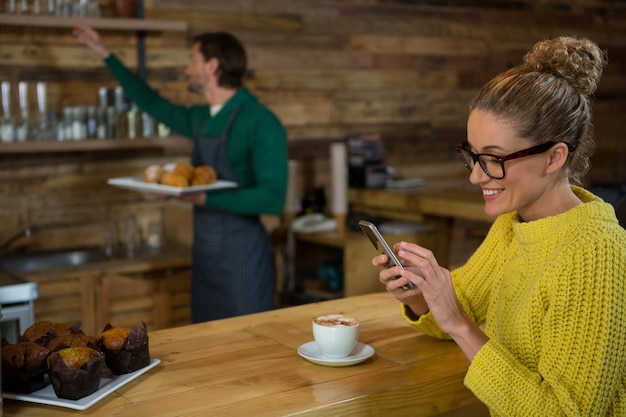 바리 스타가 커피 숍에서 백그라운드에서 작업하는 동안 휴대 전화를 사용하여 행복한 여자