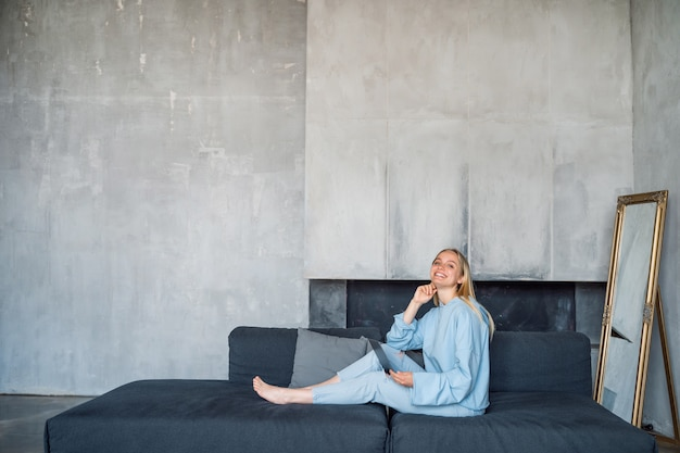 Happy woman using silver laptop while sitting on sofa