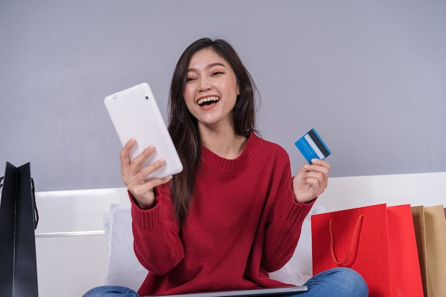 Happy woman using tablet for online shopping with credit card on bed