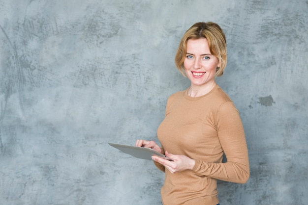 Happy woman using tablet at wall