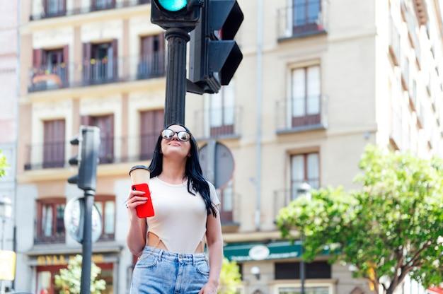 通りで携帯電話を使用して幸せな女性。