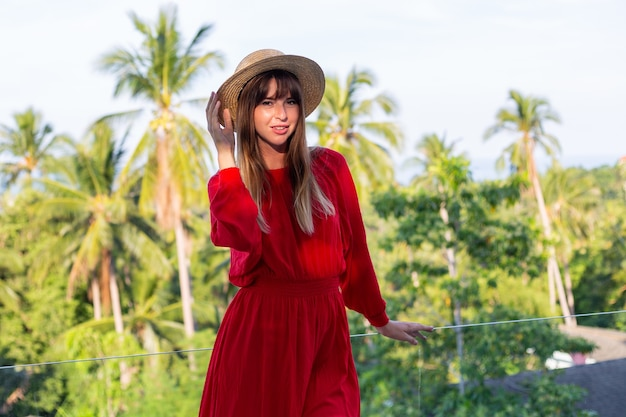 Happy woman on vacation in red summer dress and straw hat on balcony with tropical view on sea and plam trees.