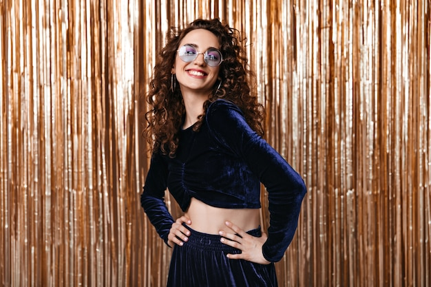 Happy woman in velvet top and round sunglasses smiling on gold background
