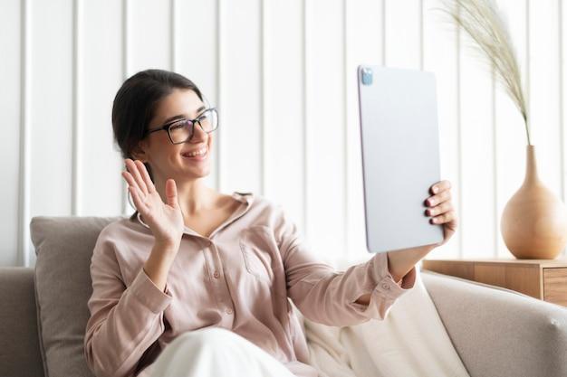 新しい通常のタブレットで呼び出す幸せな女性のビデオ
